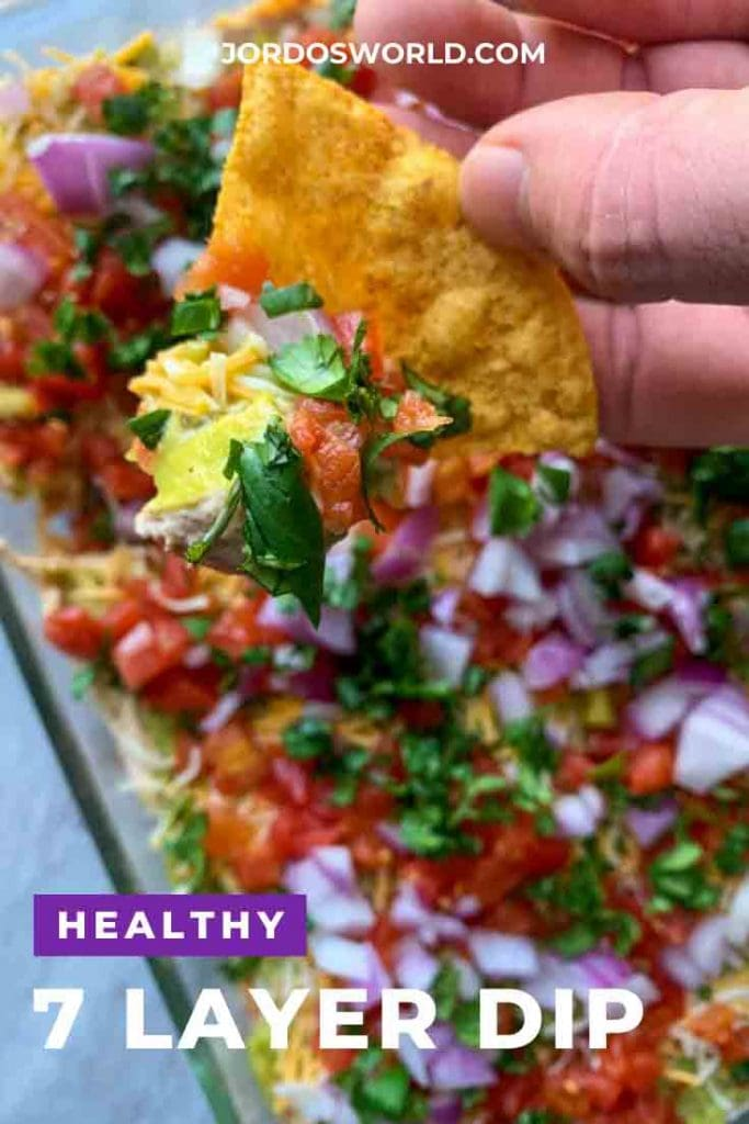 This is a picture of healthy 7 layer dip. There is a baking dish with layers of guacamole, cheese, tomatoes, red onion, and cilantro. There is a hand holding up a tortilla chip with the dip on it as well.