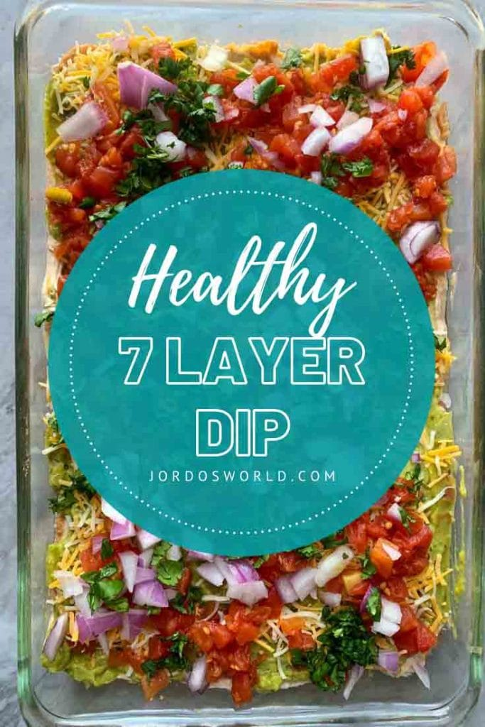 This is a picture of healthy 7 layer dip. There is a baking dish with layers of guacamole, cheese, tomatoes, red onion, and cilantro.