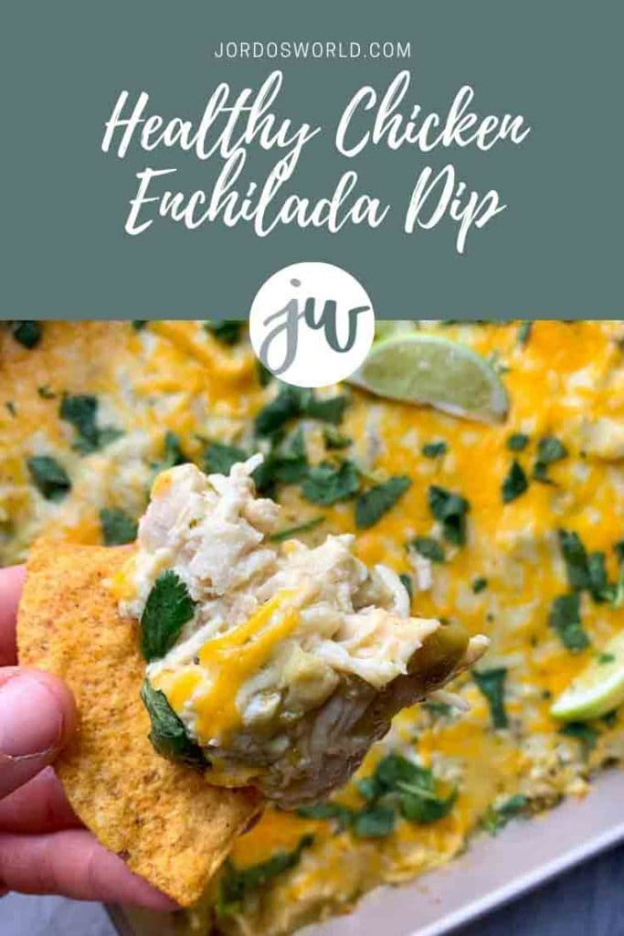 This is a pinterest pin for chicken enchilada dip. There is a pan filed with chicken and cheese dip, topped with limes and cilantro. There is a hand holding up a chip with the picture of the dip on it as well.