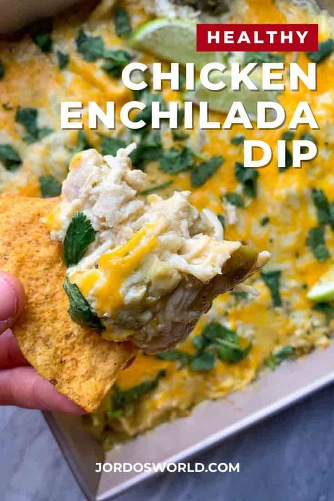This is a pinterest pin for chicken enchilada dip. There is a pan filed with chicken and cheese dip, topped with limes and cilantro. There is a hand holding up a picture of a chip with the dip on it as well.