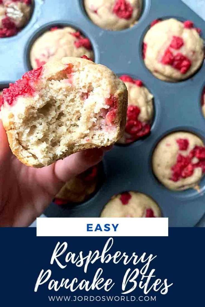 This is a pinterest pin for raspeberry pancake bites. There is a muffin tin filled with pancake bites topped with red raspberries. There is a hand holding up a pancake bite with a bite taken out of it.
