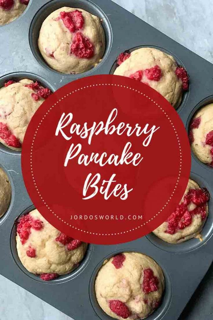 This is a pinterest pin for raspberry pancake bites. There is a muffin tin filled with pancake bites topped with red raspeberries.