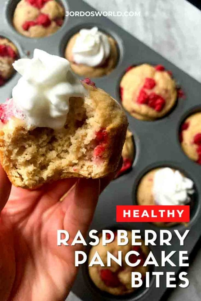 This is a pinterest pin for raspberry pancake bites. There is a muffin tin filled with pancake bites topped with red raspeberries. There is a hand holding up a pancake bite with a dollop of whipped cream on top.