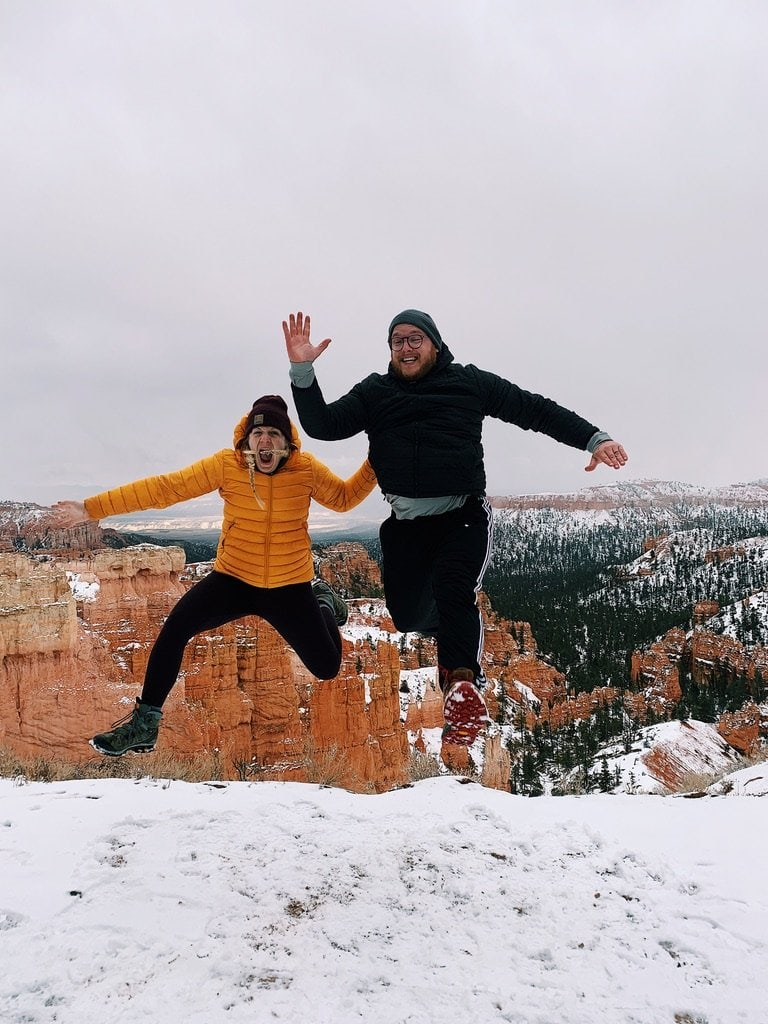 Girl in yellow coat, black leggings, maroon hat and pigtail braids along with male dressed in all black jumping in the snow at Bryce Canyon National Park.