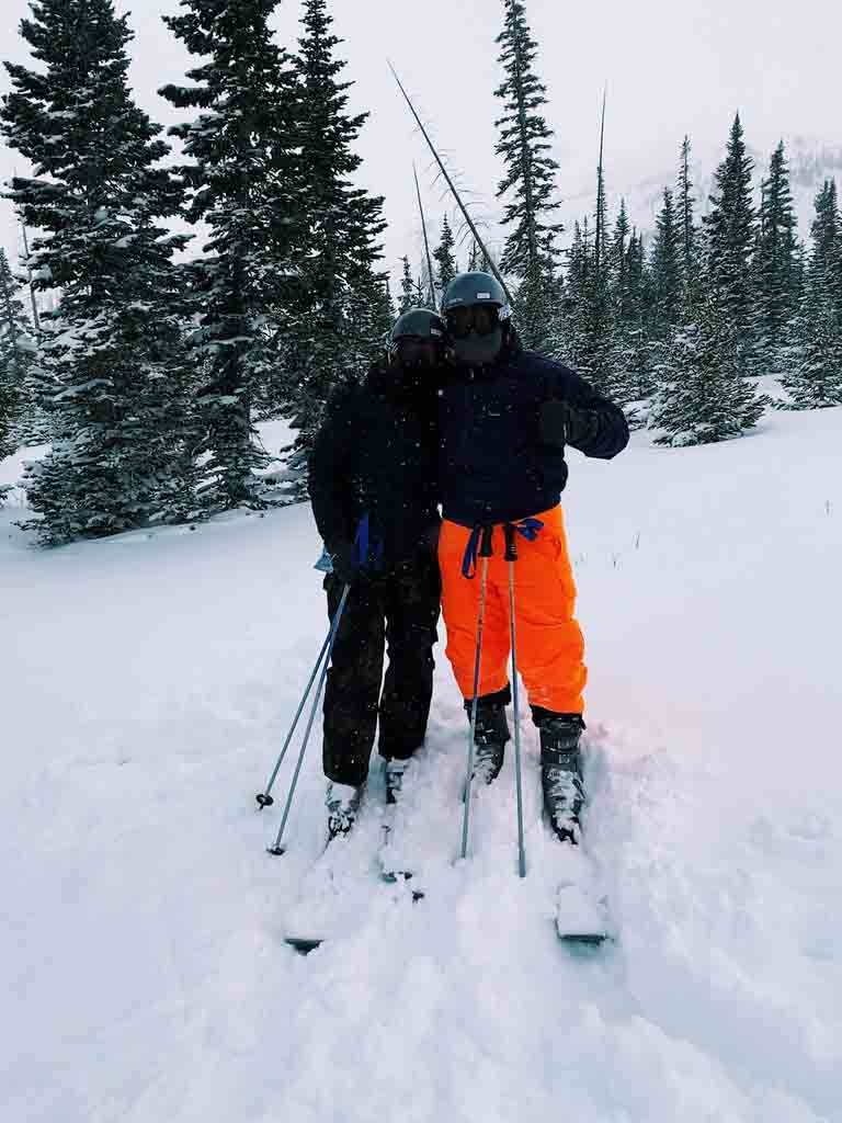 Girl in all black and boy in orange ski pants and dark coat skiing in Brian Head.