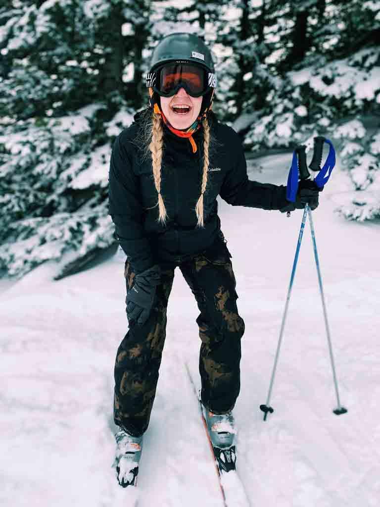 Girl in black coat and camo ski pants skiing in Brian Head, utah.