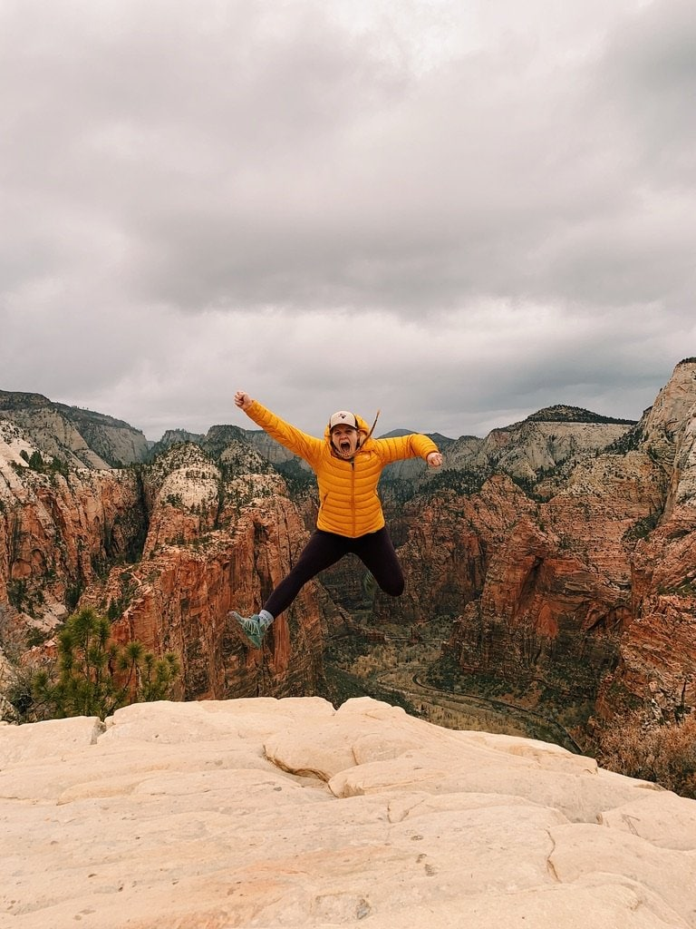 Girl in yellow coat, black leggings, trucker hat and pigtail braids jumpin in Zion National Park.
