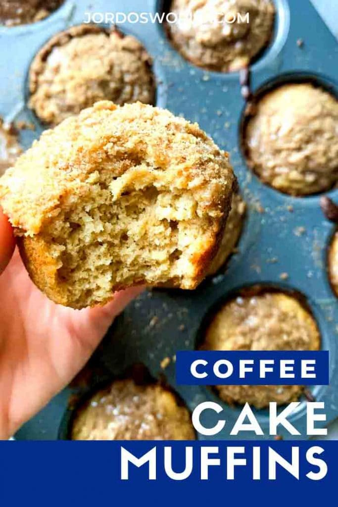 This is a pinterest pin for coffee cake muffins. There is a pan full of coffee cake muffins. There are crumbly muffins topped with icing. There is a hand holding up a muffin with a bite out of it.