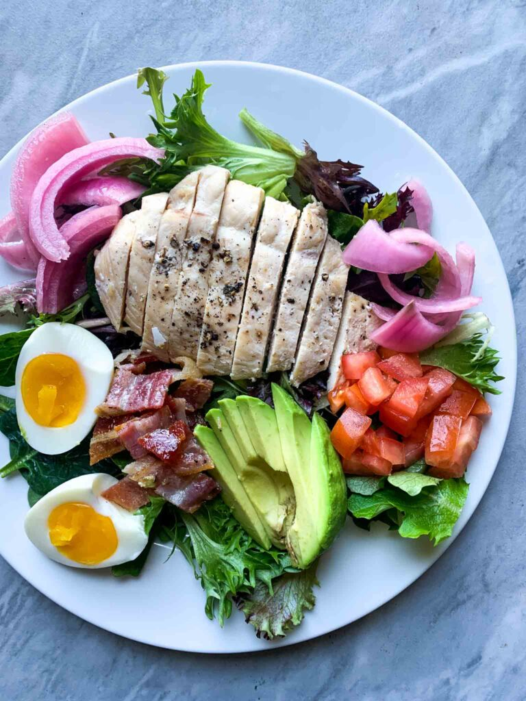 This is a panera green goddess salad. There is a plate with greens, chicken, red onion, a soft-boiled egg, bacon, tomatoes, and avocado.