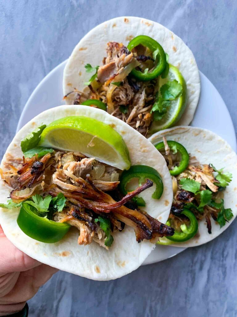 This is a picture of pulled pork on a sheet pan. There is plate with 3 small street tacos, each with pulled pork, jalapenos, limes, and cilantro. A hand is holding up one of the tacos.
