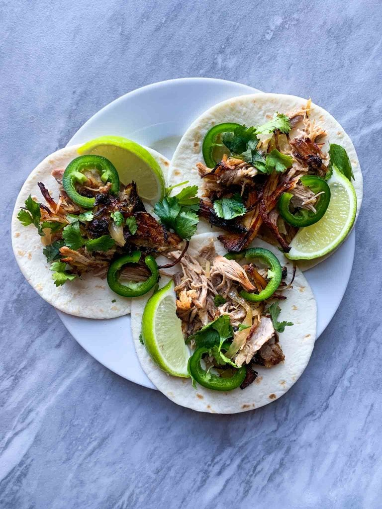 This is a picture of pulled pork on a sheet pan. There is plate with 3 small street tacos, each with pulled pork, jalapenos, limes, and cilantro.