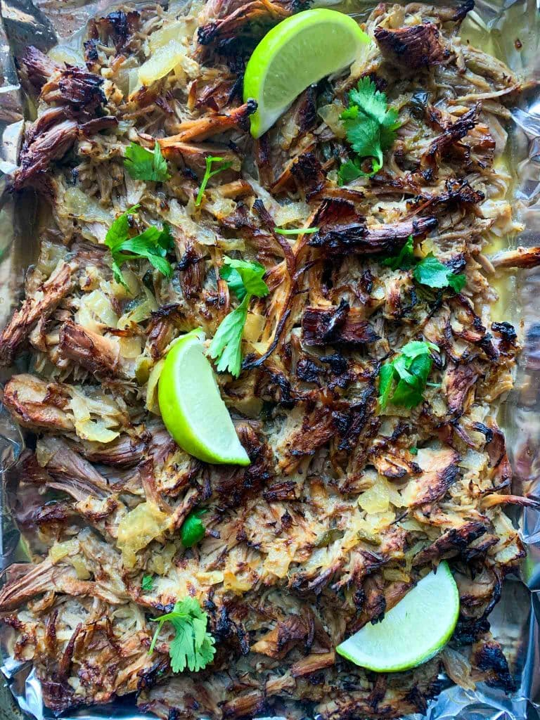 This is a picture of pulled pork on a sheet pan. There is tin foil with crispy pork topped with cilantro and limes.