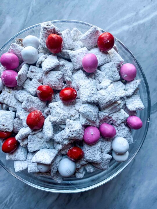 This is a bowl of Valentines Day puppy chow. There is a clear bowl with white powdered sugar chex mix and valentines m&m's mixed in.