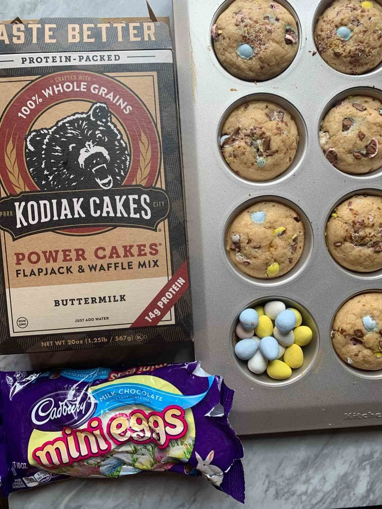 These are the ingredients for the easter pancakes. There's a muffin tin with the pancake bites, a box of Kodiak Cakes pancake mix, and a bag of Cadbury mini eggs.