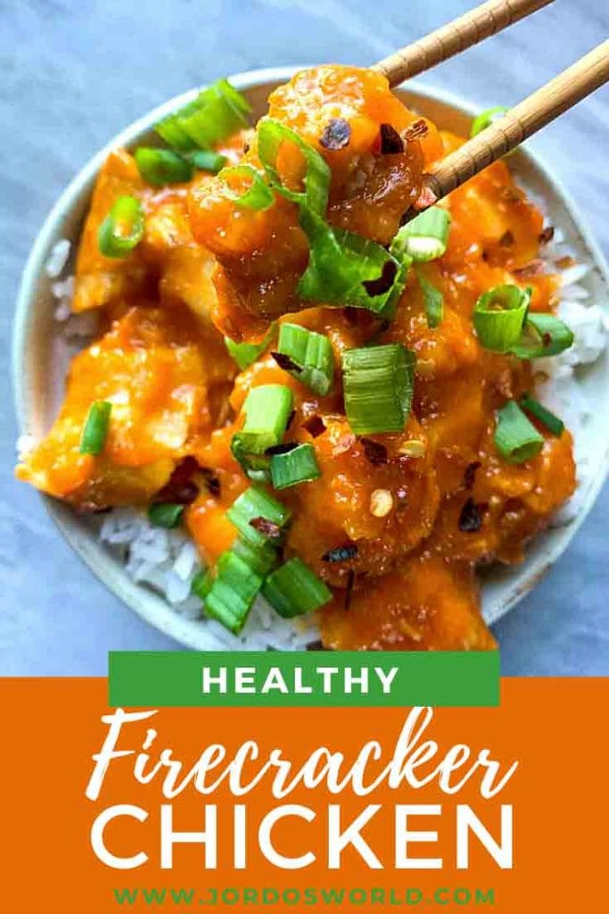 This is a bowl of firecracker chicken. There is a cream color bowl with white rice, topped with orange chicken and green onions on top.