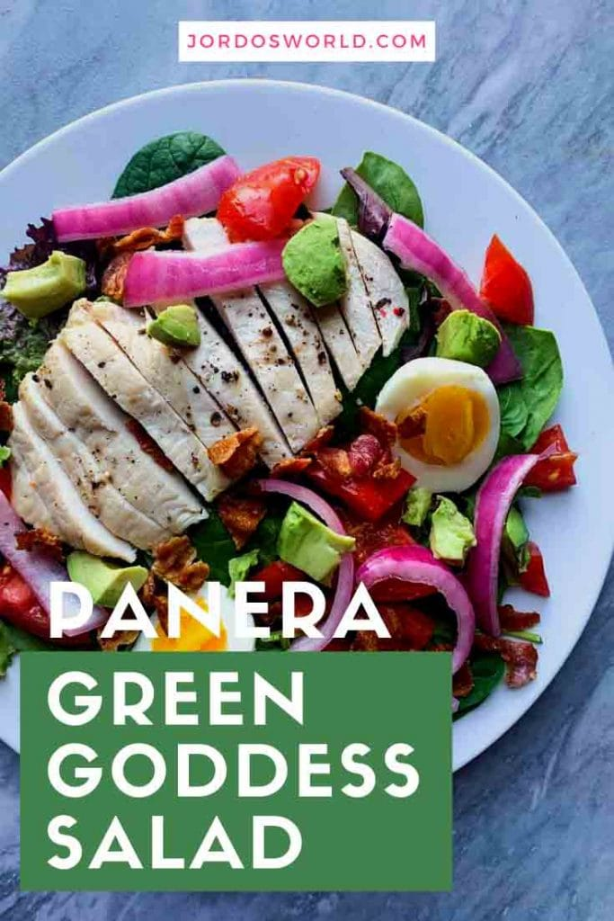 This is a copy cat panera green goddess cobb salad. There is a big white pate topped with mixed greens, sliced chicken breast, diced tomatoes, red onions, bacon, avocado, and a hard boiled egg.
