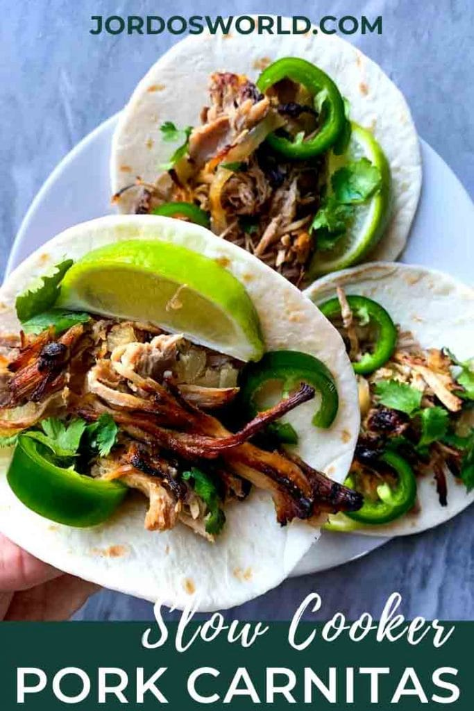 This is a picture of pork carnitas. There are two carnitas on a plate and one being held up by a hand. Each carnita is a small flour tortilla topped with shredded pork, jalapenos, limes, and cilantro.