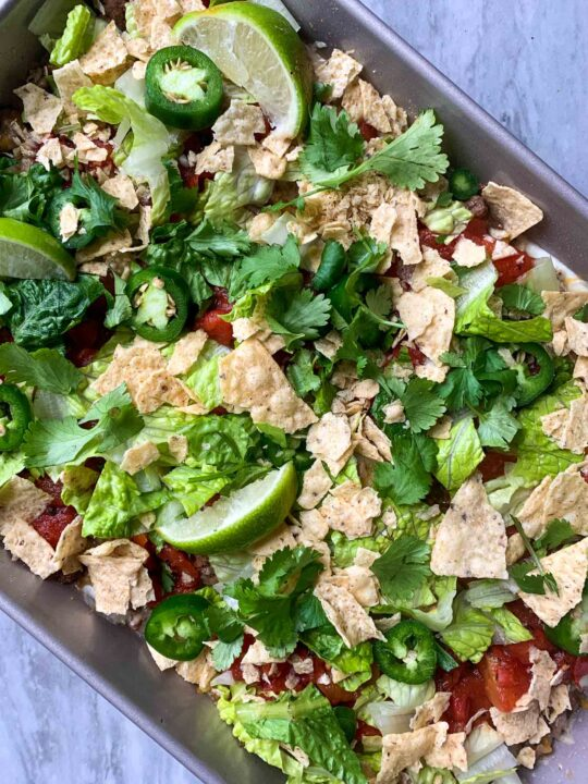This is a picture of taco casserole. There is a pan with layers of beans, greek yogurt, lettuce, tomatoes, tortilla chips, cilantro, jalapenos, and limes.