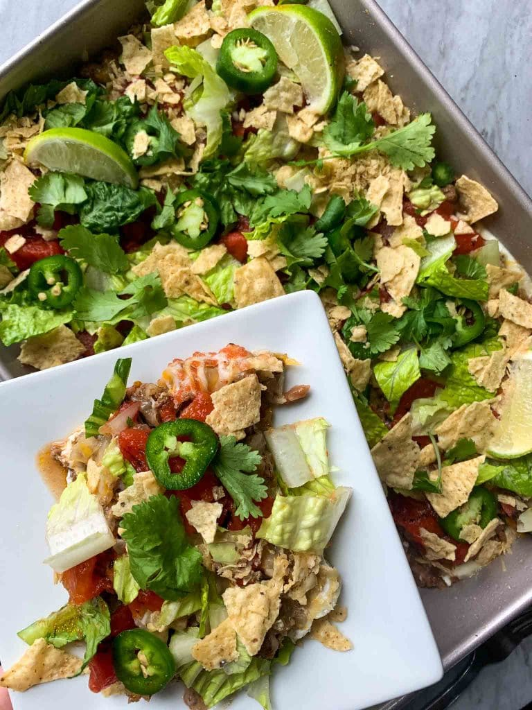 This is a picture of taco casserole. There is a pan with layers of beans, greek yogurt, lettuce, tomatoes, tortilla chips, cilantro, jalapenos, and limes. There is also a small white plate with a serving of casserole on it.