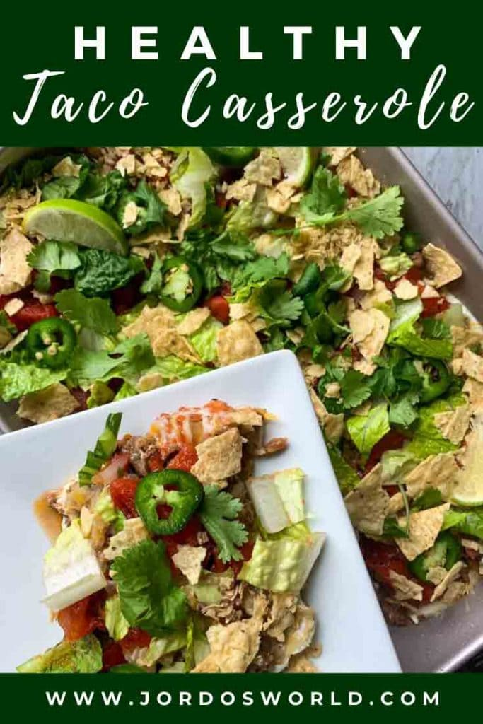 This is taco casserole. There is a plate with the casserole held above a baking dish with the rest of the casserole. The casserole is layers of meat, taco seasoned greek yogurt, lettuce, tomatoes, chips, cheese, and cilantro topped with jalapenos and limes.