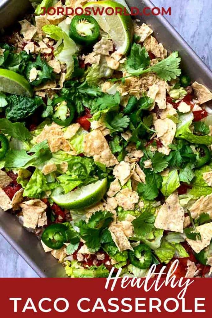 This is taco casserole. There is a baking dish full of the casserole. The casserole is layers of meat, taco seasoned greek yogurt, lettuce, tomatoes, chips, cheese, and cilantro topped with jalapenos and limes.