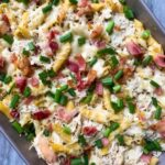 This is a casserole dish filled with chicken bacon ranch casserole. There are penne noodles with shredded chicken, chopped bacon, and melted cheese on top. Chopped green onions are covering the top.