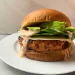 These are the chipotle lime turkey burgers. There is a patty with cheese, spinach, avocado, sauce, and a bun.