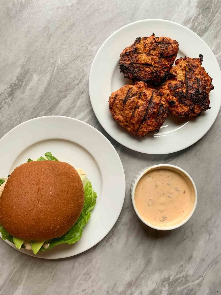 These are the chipotle lime turkey burgers. There is a plate of turkey burger patties, plate with a turkey burger, and side of sauce.