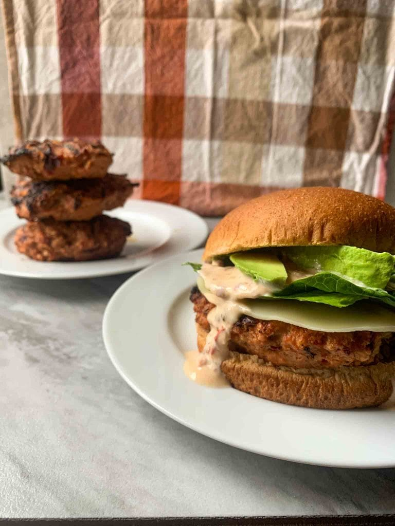 These are the chipotle lime turkey burgers. There is a patty with cheese, spinach, avocado, sauce, and a bun. There is also a stack of turkey burgers in the back.