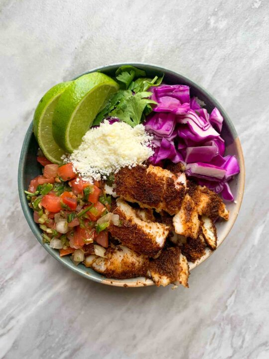 This is an easy fish taco bowl. There is a small bowl with sliced fish, pico, cojita cheese, red cabbage, lines, and cilantro. It's very colorful!