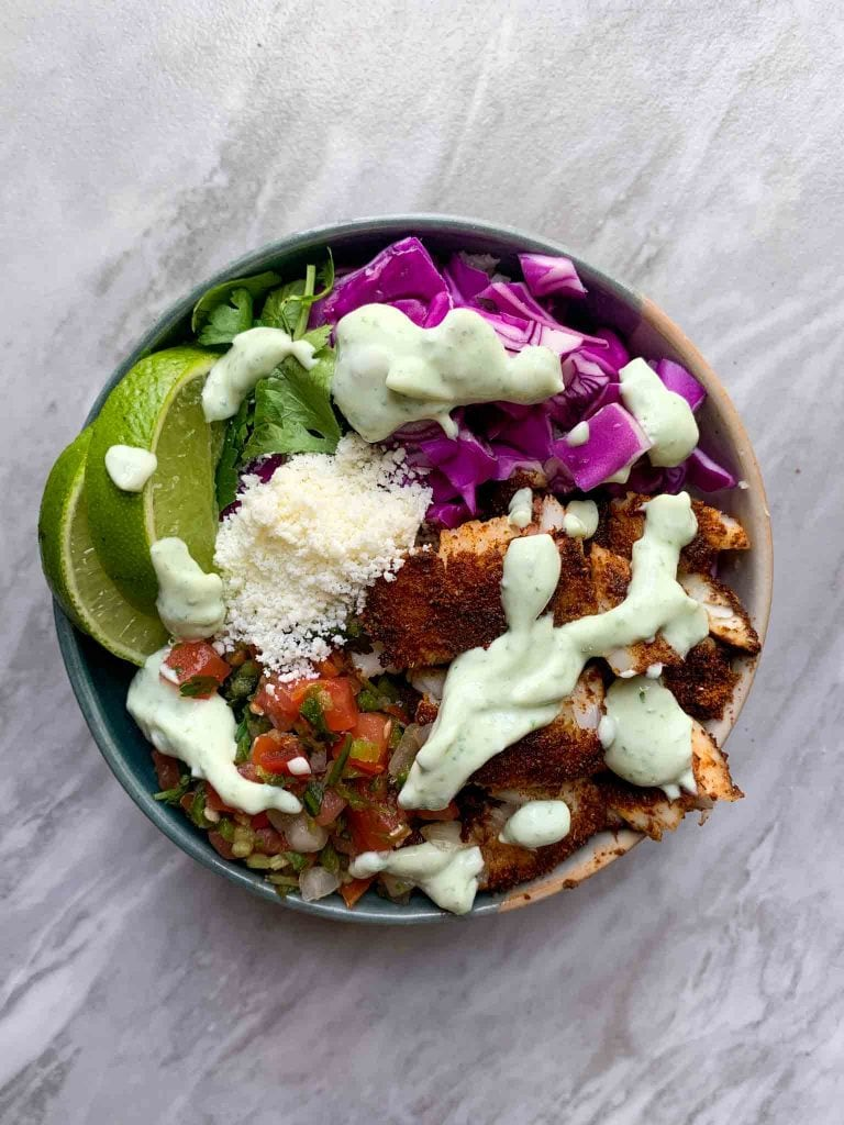 This is an easy fish taco bowl. There is a small bowl with sliced fish, pico, cojita cheese, red cabbage, lines, and cilantro. It's very colorful! There is a cilantro lime dressing on top.
