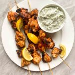 These are greek lemon chicken skewers. There are 4 wooden skewers with cripsy chicken pieces on each. There are seasonings and lemon slices on the skewers as well. There is also a small white bowl filled with creamy tzaziki sauce.