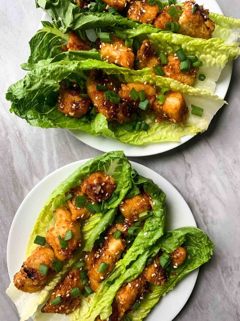 These are sesame chicken lettuce wraps. There are big pieces of lettuce with pieces of toasted sesame chicken. The chicken is orange and brown and topped with sesame seeds and green onions. There are two plates with 3 lettuce wraps on each plate.