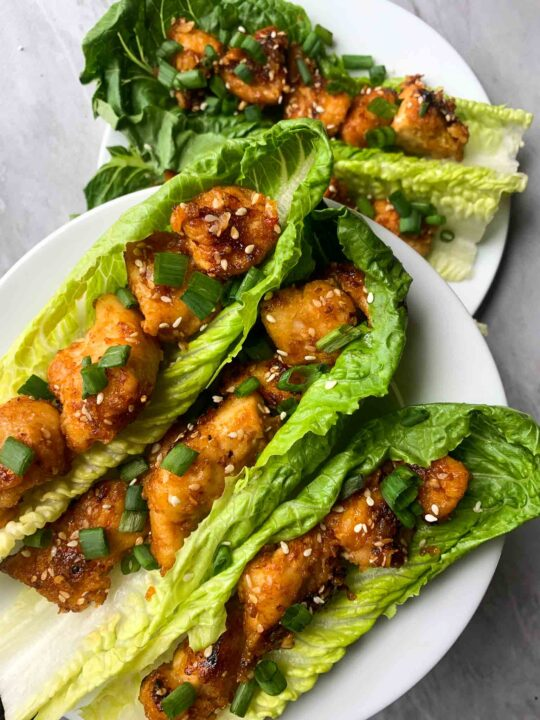 These are sesame chicken lettuce wraps. There are big pieces of lettuce with pieces of toasted sesame chicken. The chicken is orange and brown and topped with sesame seeds and green onions.