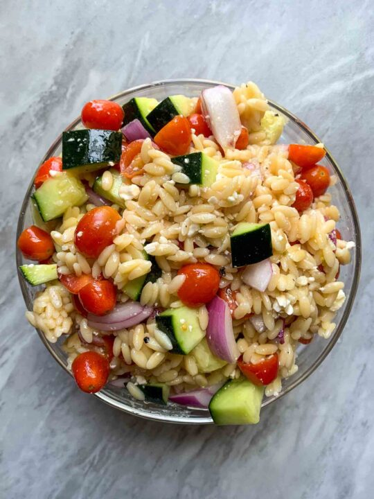This is a bowl of summer orzo pasta bowl. There is orzo with halved tomatoes, cucumber pieces, diced red onions, cheese, and a light dressing on top.