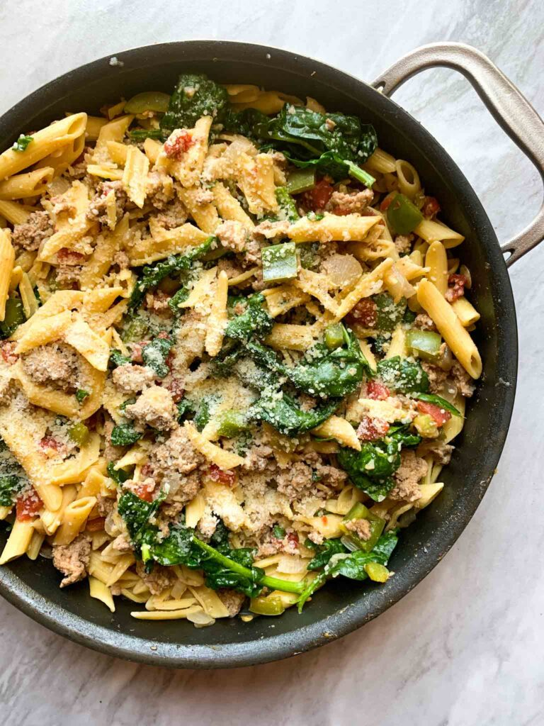 This is a big skillet of turkey pasta primavera. There are penne noodles with spinach, tomatoes, chiles, and turkey mixed on. Parmesan cheese is sprinkled on top.