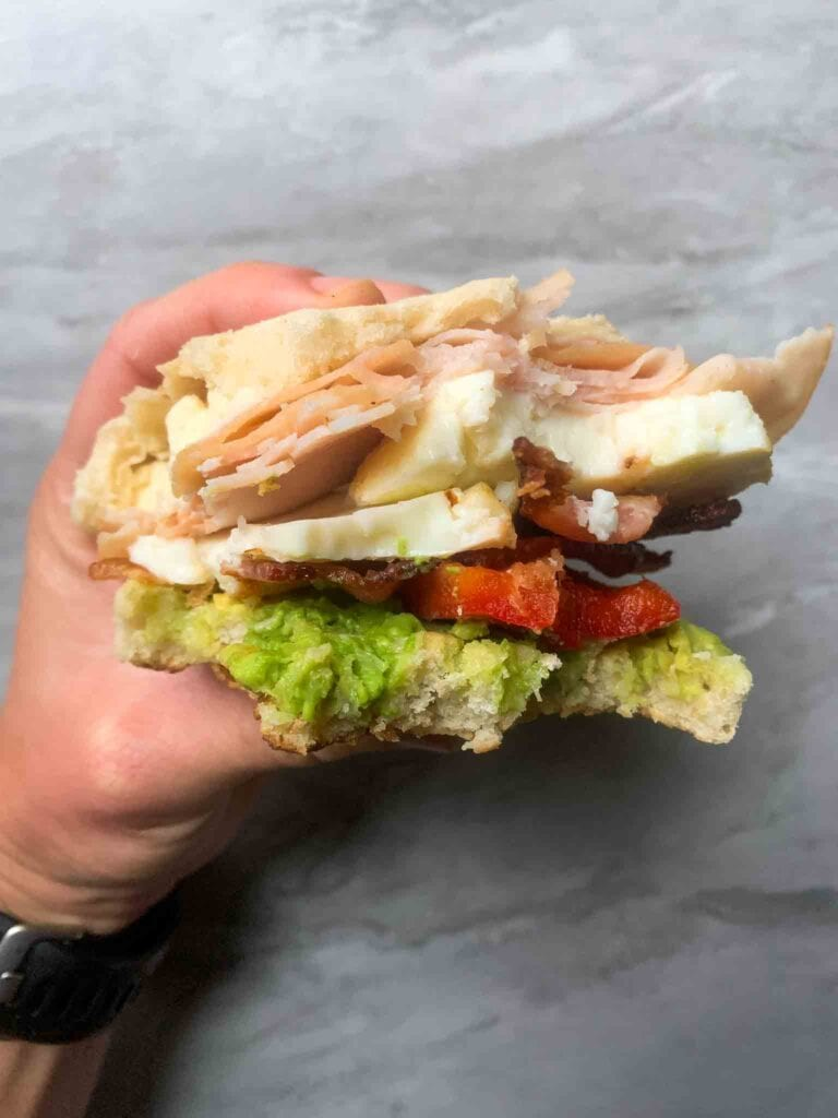 This is a breakfast club sandwich. There is an english muffin, avocado, tomato, bacon, turkey, egg white, and cheese. The sandwich is held in a hand with bites taken out of it so you can see the layers.