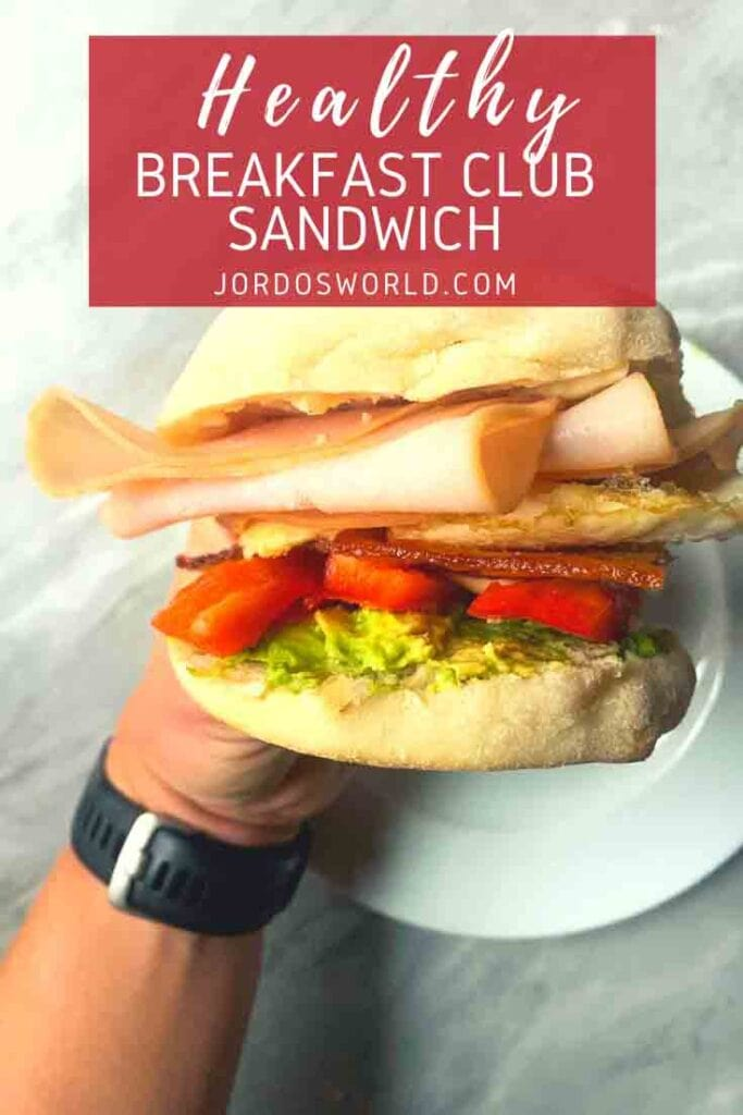This is a pinterest pin of a low-carb breakfast club sandwich. There is a hand holding up a sandwich with an english muffin, turkey slices, egg whites, bacon, tomatoes, cheese, and avocado.