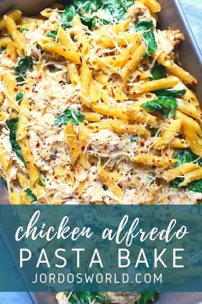 This is a pinterest pin for the chicken alfredo pasta bake. There is yellow penne pasta topped with shredded parmesan and red pepper flakes with spinach mixed in.