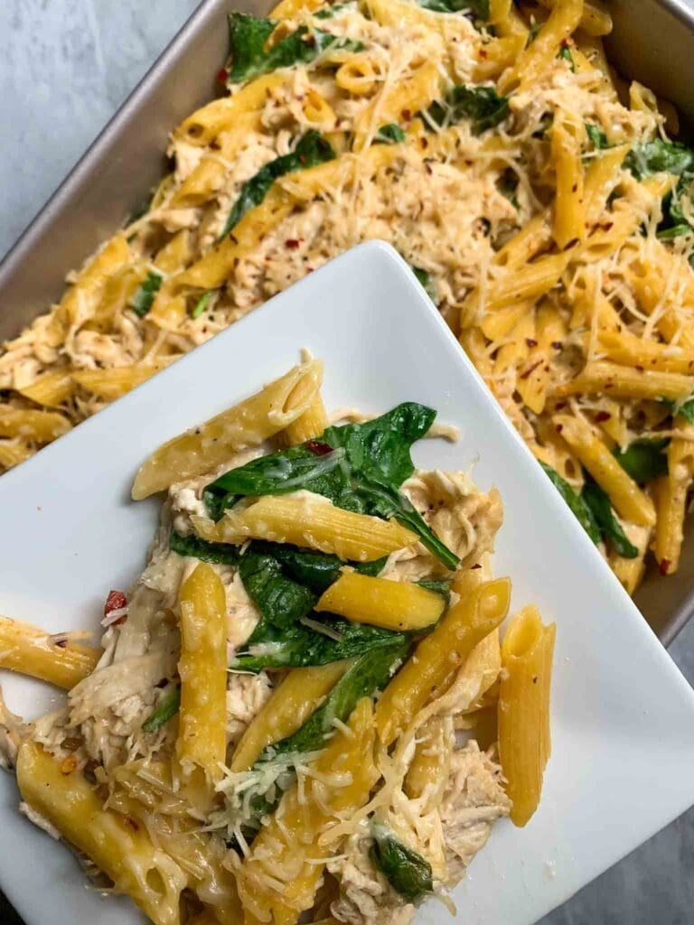 This is a casserole dish filled with chicken alfredo pasta bake. There is yellow penne pasta topped with shredded parmesan and red pepper flakes with spinach mixed in. There is a small white plate with a scoop of the casserole.