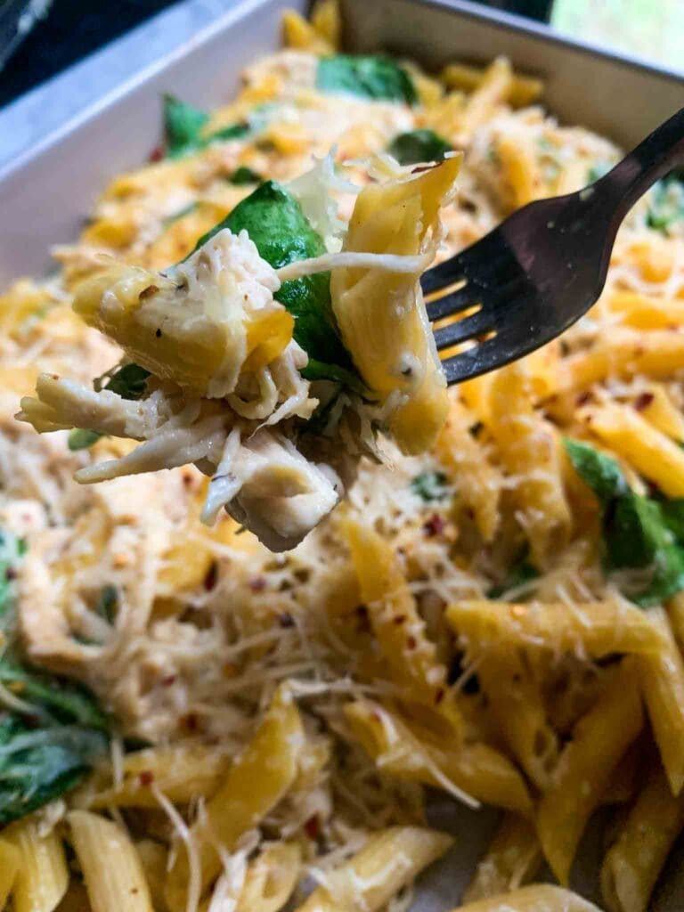 This is a casserole dish filled with chicken alfredo pasta bake. There is yellow penne pasta topped with shredded parmesan and red pepper flakes with spinach mixed in. There is a fork with a bite of the casserole.