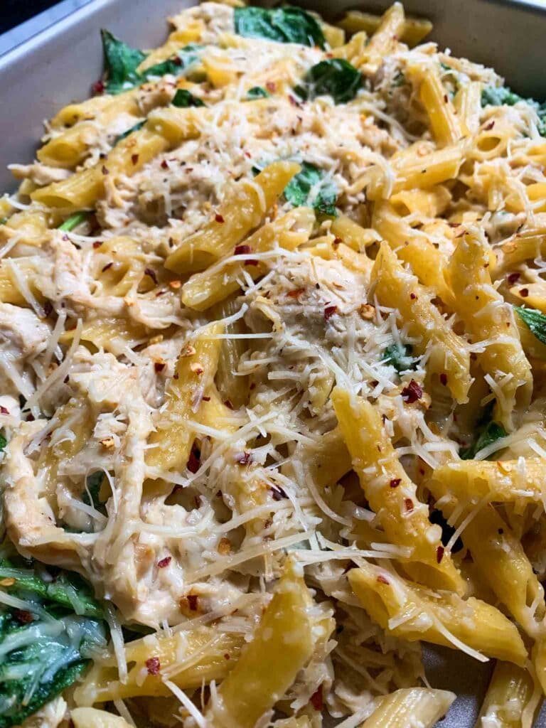 This is a casserole dish filled with chicken alfredo pasta bake. There is yellow penne pasta topped with shredded parmesan and red pepper flakes with spinach mixed in.