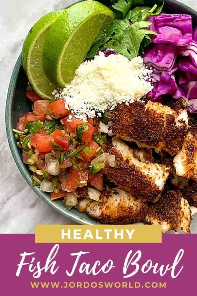 This is a pinterest pin for a fish taco bowl. There is a small bowl with cauliflower rice but it can't be seen because of the toppings. There is spiced fish pieces, red onion, cilantro, cotija cheese, pico de gallo, and limes, all sectioned out in the bowl.