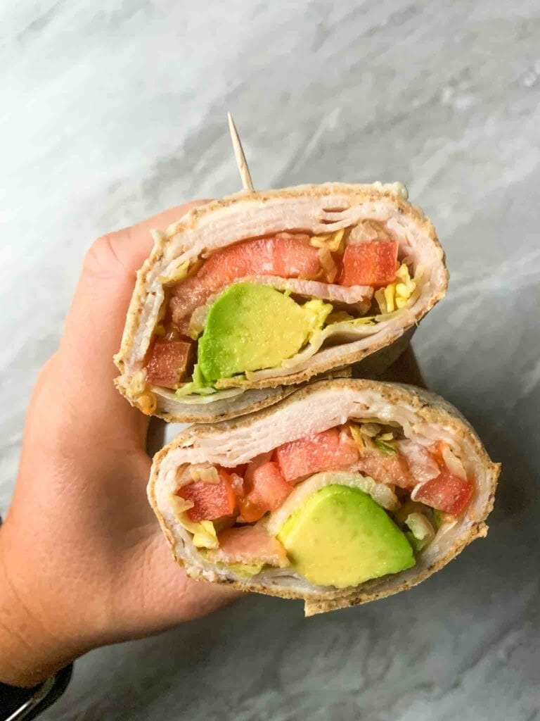 This is the california turkey club wrap. There is a wrap with layers of turkey, cheese, tomato, bell pepper, lettuce, and avocado. The wrap is cut into half and held together with a toothpick and one hand.