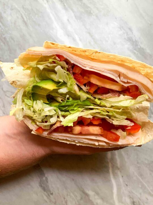This is the california turkey club wrap. There is a wrap with layers of turkey, cheese, tomato, bell pepper, lettuce, and avocado. Two hands are holding this wrap together.