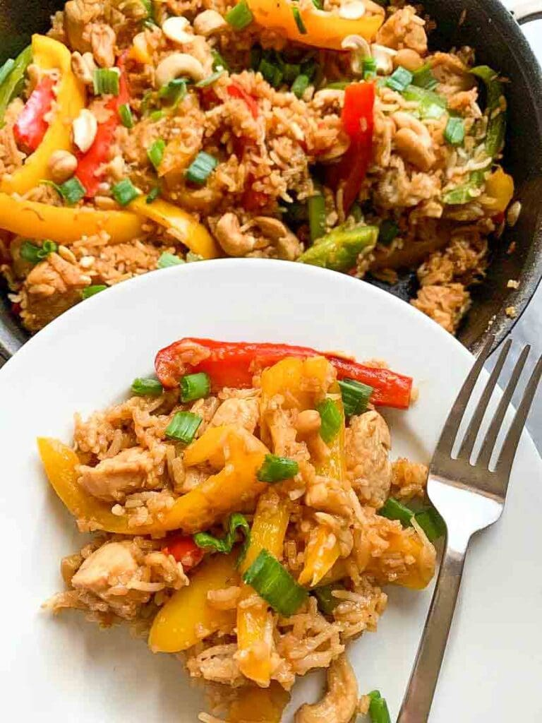 This is cashew chicken stir fry. There is a skillet filled with rice, bell peppers, chicken, green onions, cashews, and a sauce. There is a small white place with the cashew chicken stir fry and a fork.