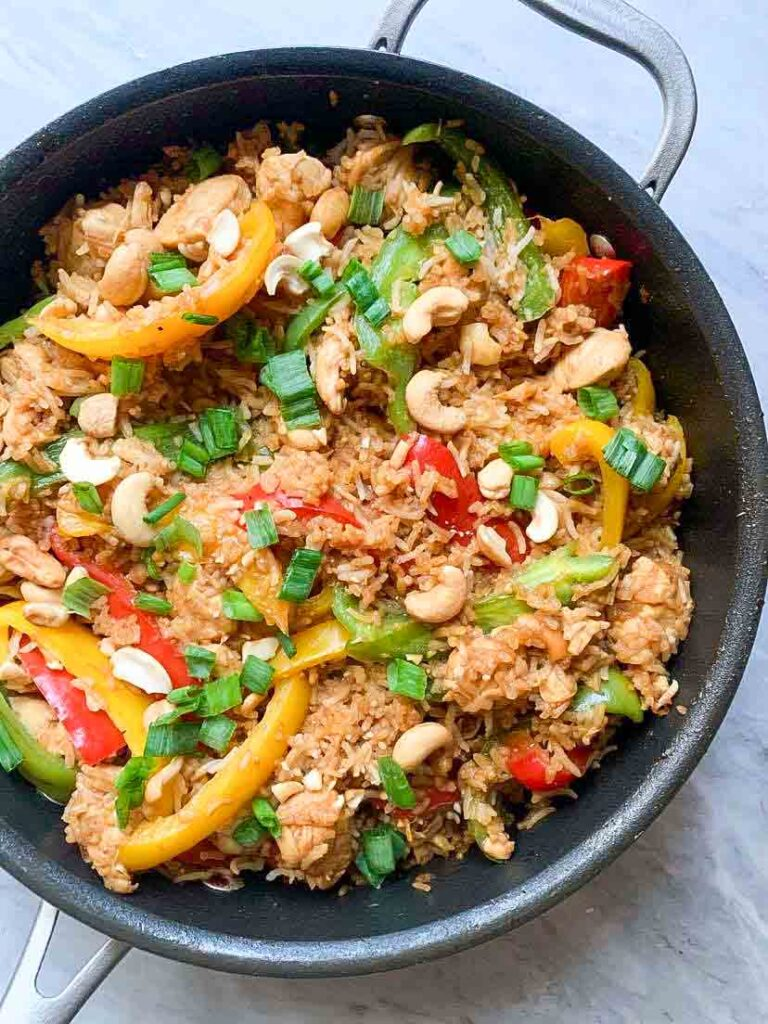 This is a skillet full of healthy cashew chicken stir fry. There is a mixture of rice, colorful bell peppers, green onions, cashews, and a sauce.