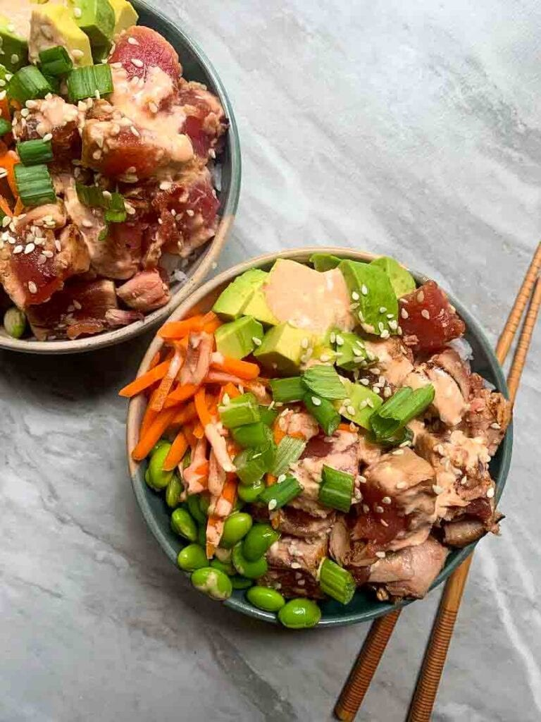 This is an ahi tuna poke powl. There is a ceramic bowl with tuna pieces, green onion, avocaod, edamame, carrots, sauce, and sesame seeds. There's a pair of chopsticks next to the bowl as well.