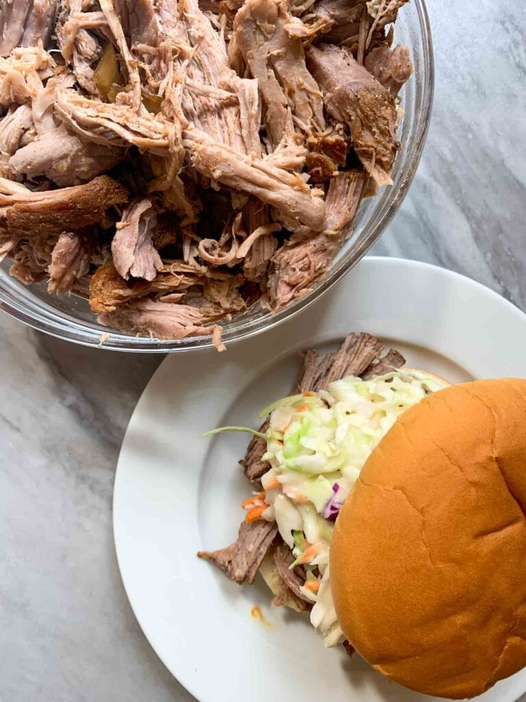 There is a plate with a pulled pork sandwich. There is a toasted bun, pulled pork, and slaw, with a bowl of pulled pork in the back.