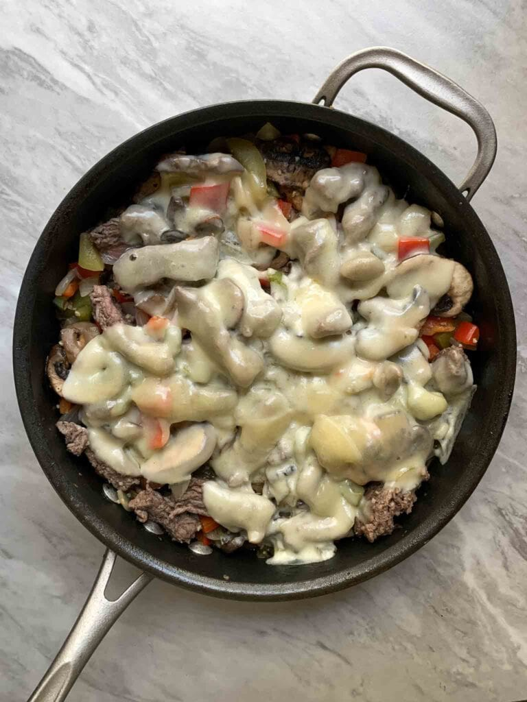 This is a philly cheesesteak skillet. There is a skillet filled with pieces of steak, bell peppers, and onions, all topped with melted cheese.